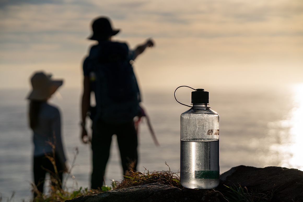 Man and child hikers silhouetted against sunny skies with drink bottle in foreground.