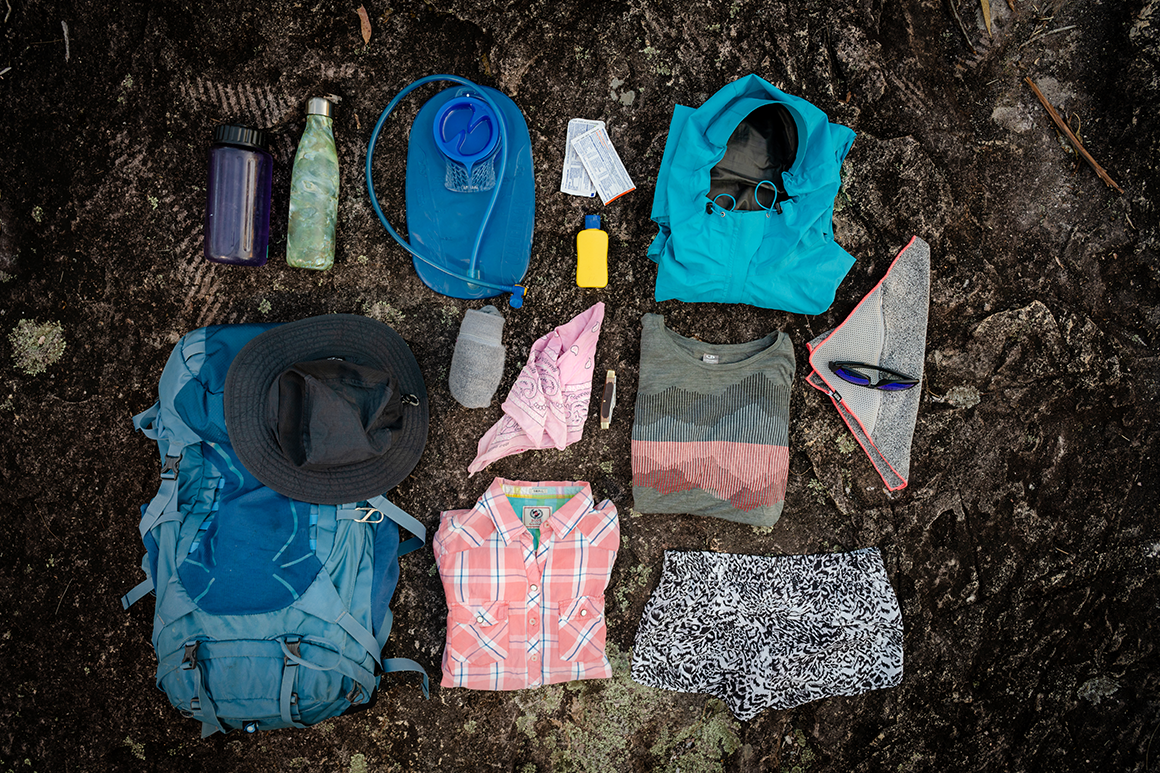 Hiking gear such as water bladder, bottle, bandana, sunscreen laid out on a rock.