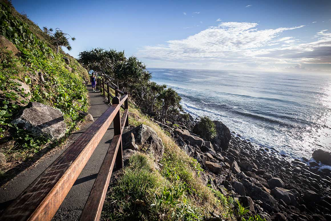 On a steep cliff that drops to a rocky shore and the ocean's edge, a person walks along sealed track (with handrail) that winds around the cliff-face.