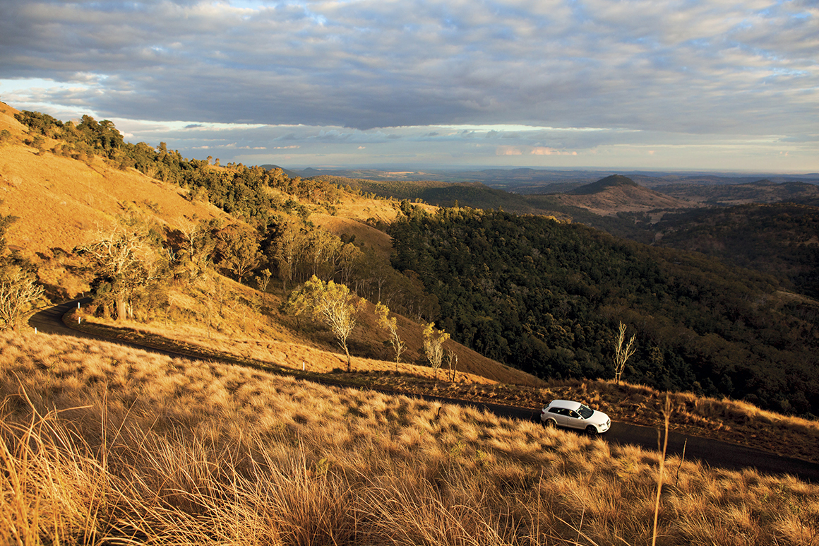 Distant mountain range lies in shadow under a cloudy blue sky and a white car travels along a road winding around a grassy hillside, bathed in the golden glow of late afternoon light.