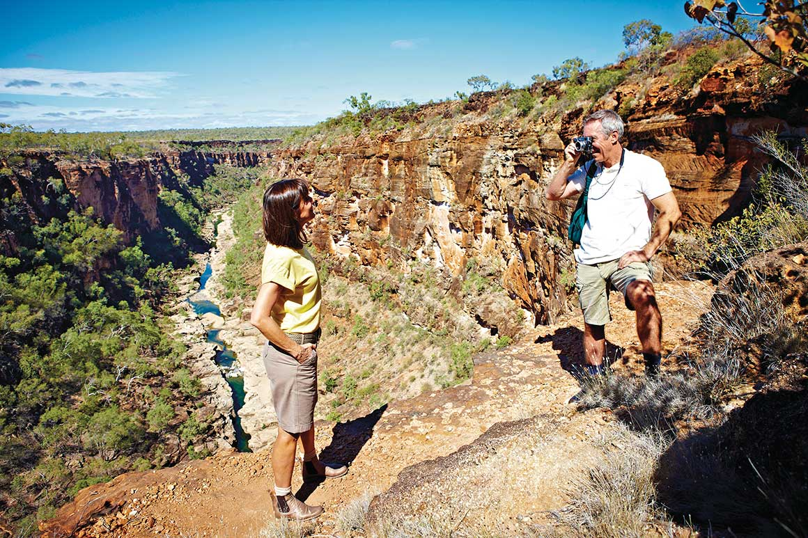 A man and a woman pose for photos on walking track that descends into deeply-incised gorge, where narrow creek runs along floor of the gorge.