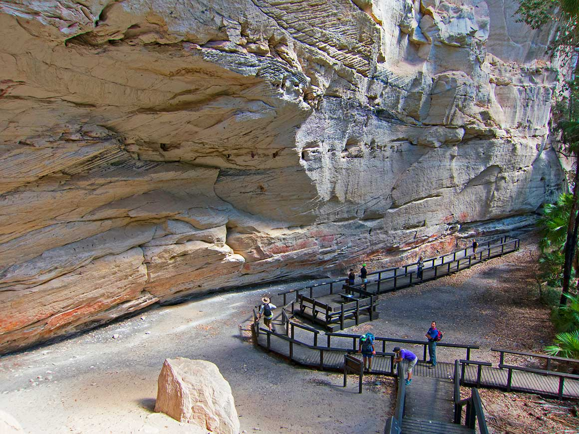 A low boardwalk winds alongside a massive vertical white sandstone rock face adorned with Aboriginal rock art in red ochre, with visitors variously reading signs and gazing at the imagery.