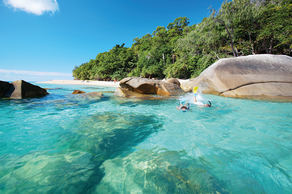 Clear blue waters lap smooth granite boulders with two snorkelers exploring shallows.