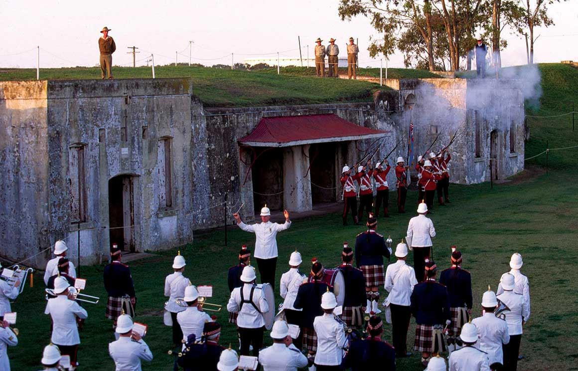 Musicians in period costume play in front of ruins with canons firing.