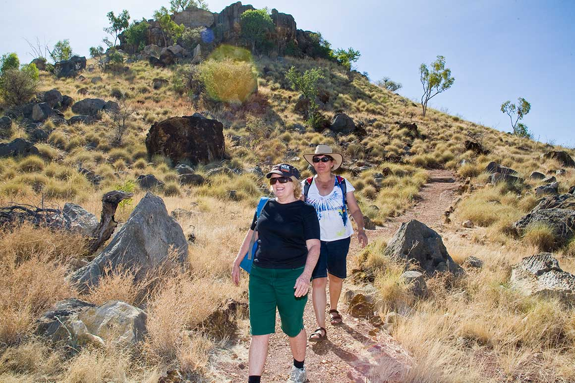 Two visitors walk along a rocky track winding down a gently sloping hill in a dry savanna landscape, with sparse trees and jagged rocks protruding above the yellow grass.