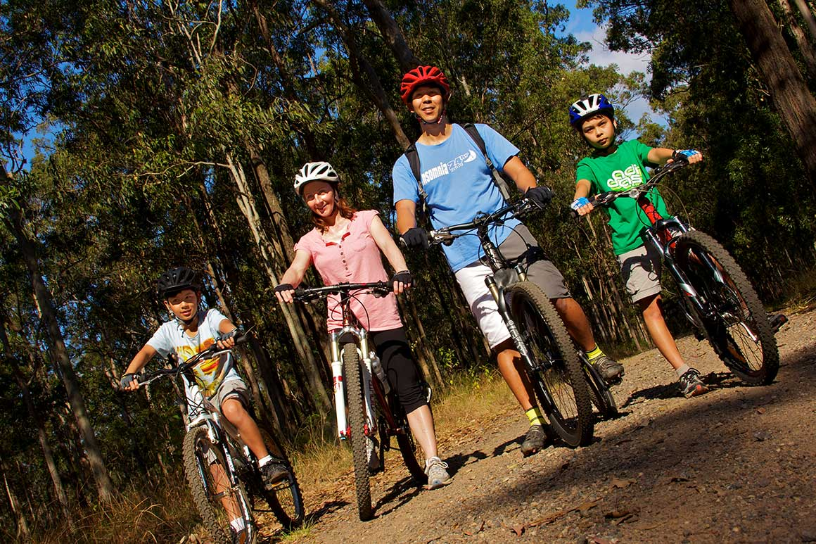 Family of two adults and two kids in their helmets on their bikes on a wide mountain bike trail surrounded by gum trees.