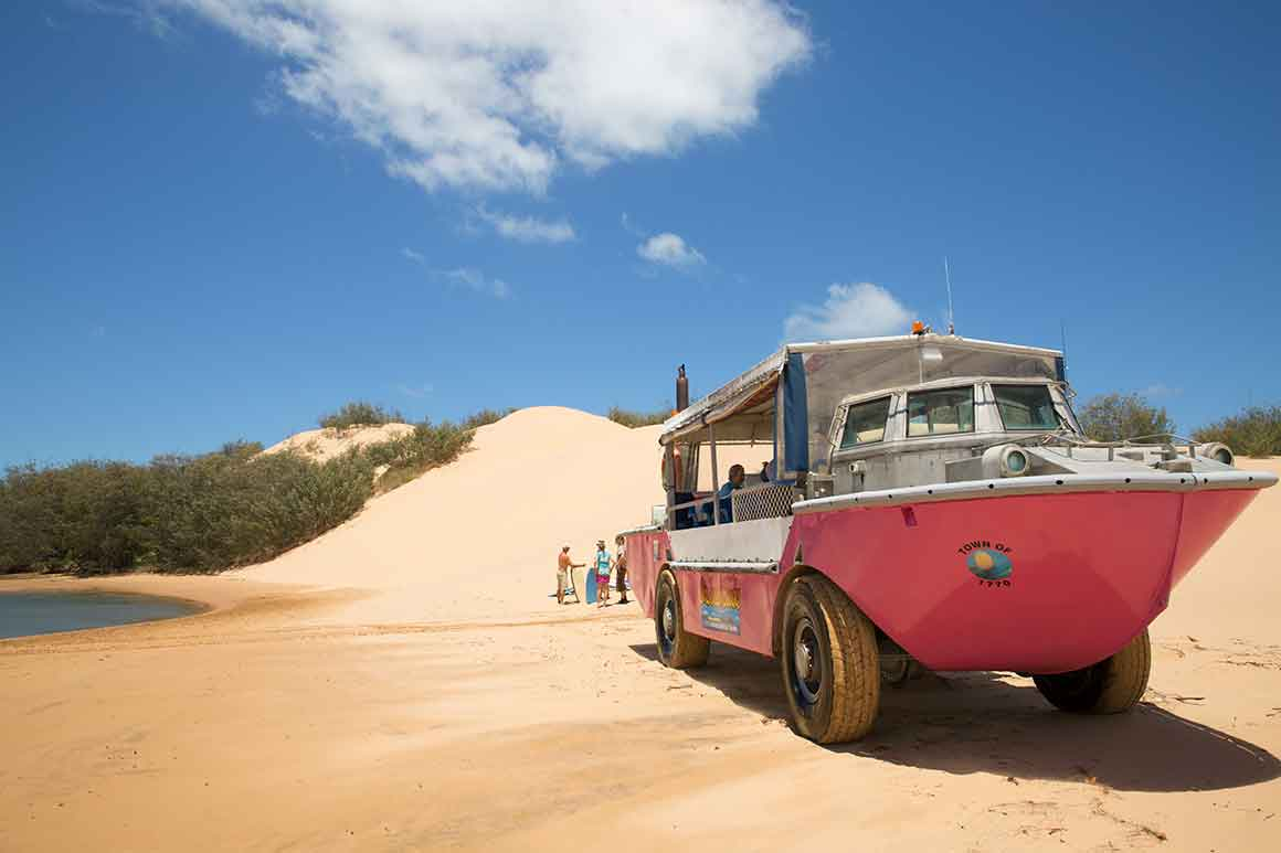 A bright red boat on wheels drives across a sandy beach with dunes in the background.