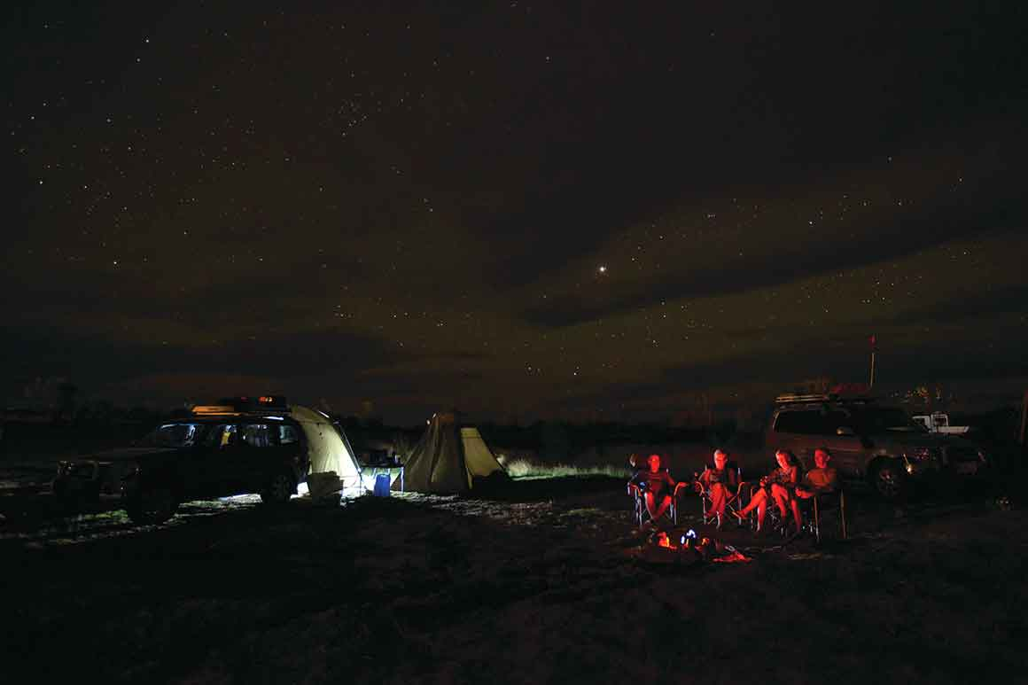 In the blackness of night, four friends sit in camp chairs around a camp fire, bathed in the red glow of the fire, with two cars parked nearby and starry skies overhead.