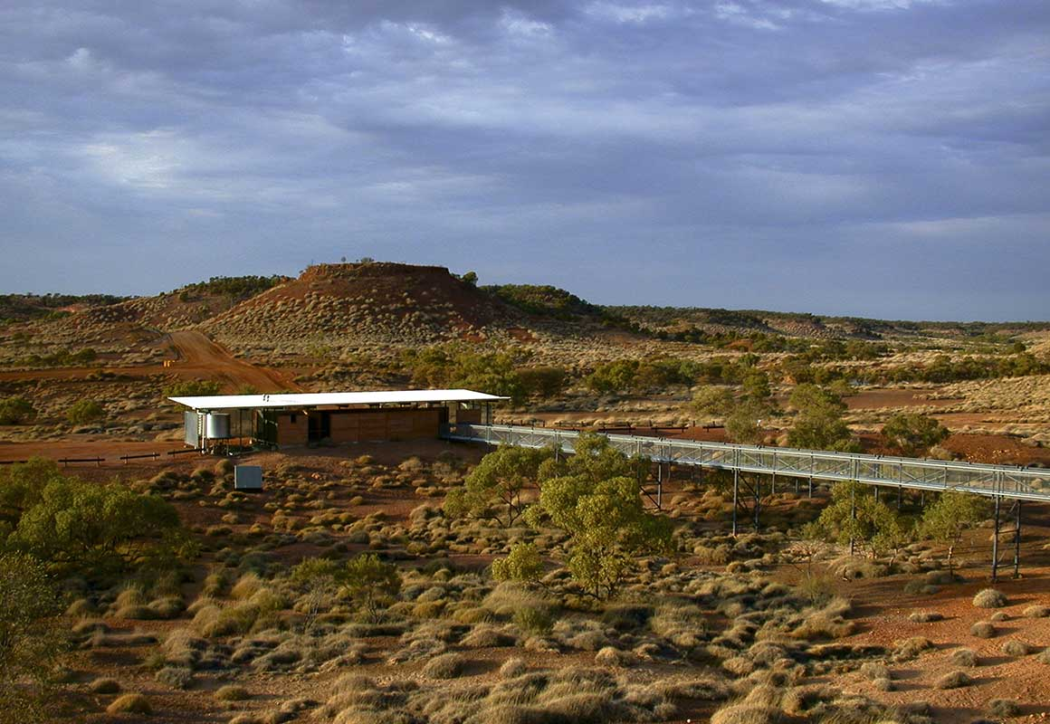 Solar powered building and long walkway nestled in an expansive savanna landscape dotted with spinifex.