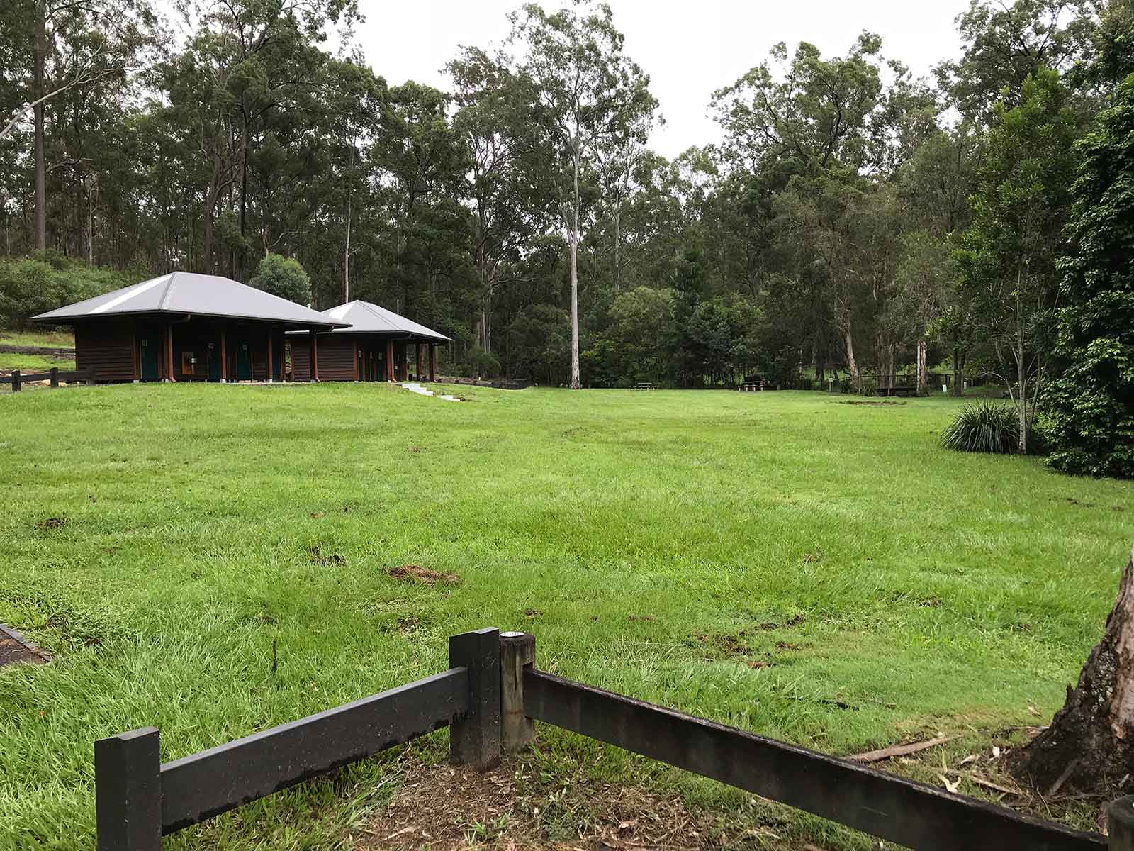 Large rolling open grassy space fringed by forest, with a picnic shelter on a slight rise.