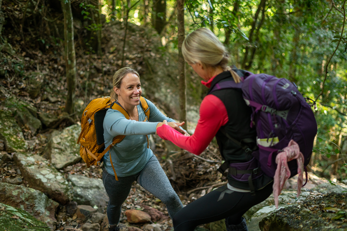 Two hikers help each other over uneven terrain.