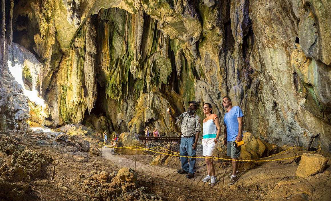 Ranger and two visitors stand on the marked track in the middle of a large underground chamber with rock features in the background.