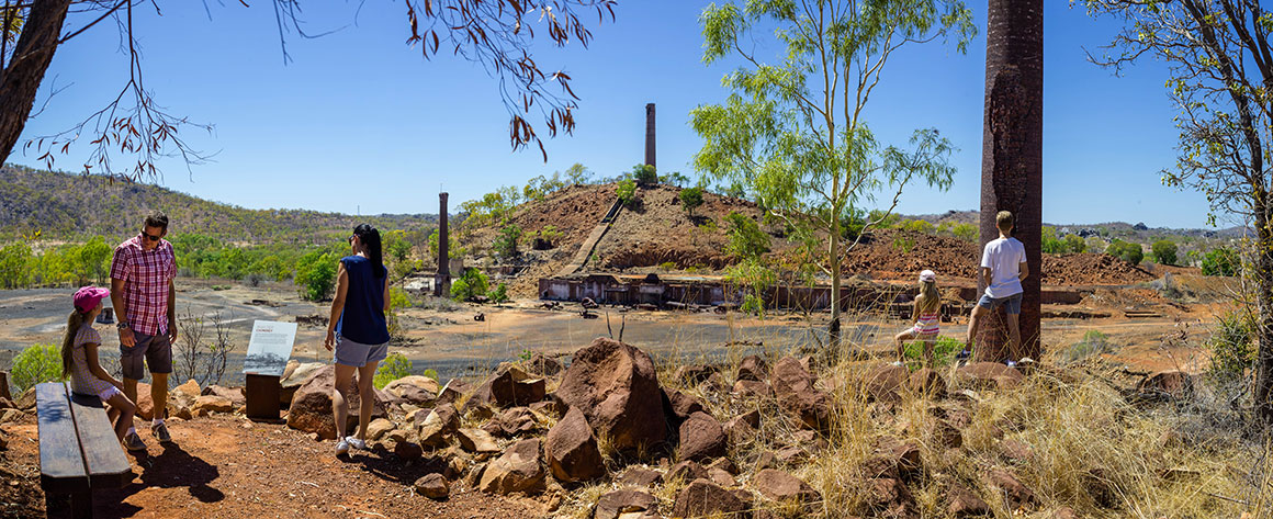 A family group sit at a viewing point overlooking the ruins and three tall chimneys stacks against a blue sky and outback landscape