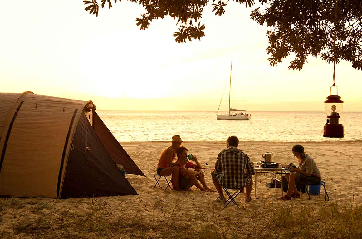 Group of young people sit on camp chairs on beach sand, near their dome tent, at sunset, with calm ocean waters in the background.