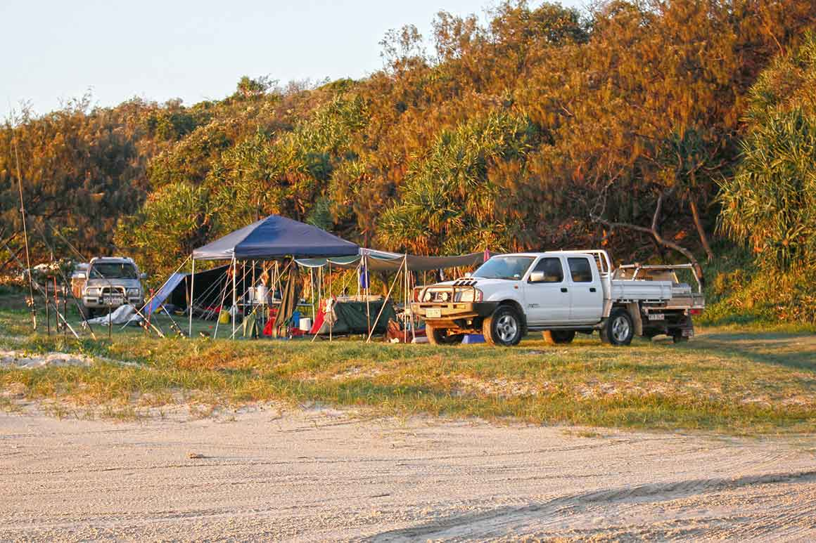 Two four-wheel drives are parked near two pop-up shalters with assorted cmaping gear, near the beach with a backdrop of coastal vegetation, all bathed in the golden light of late afternoon.