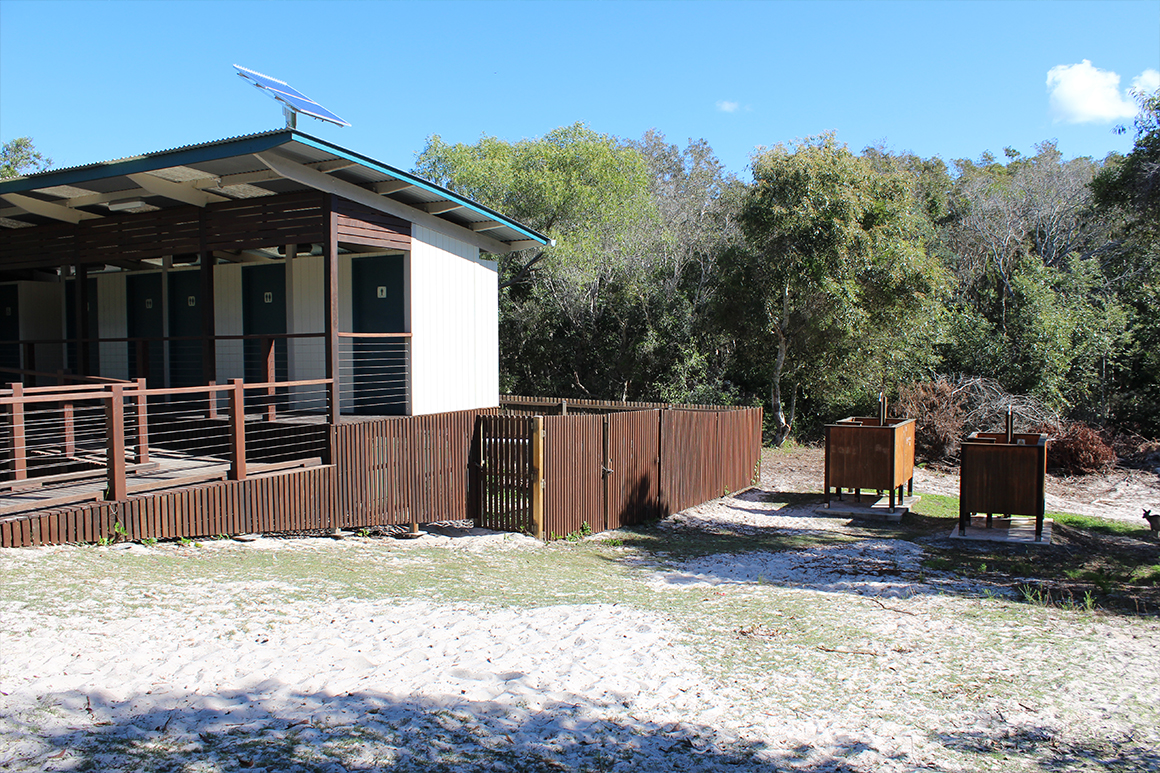 An amenities block with wooden outdoor showers is located in a sandy open area.