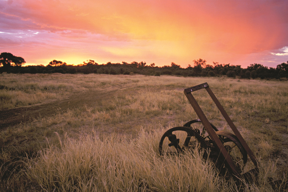 An old rusty farm implement sits in a paddock of dry grass against a backdrop of orange purple skies at sunset.