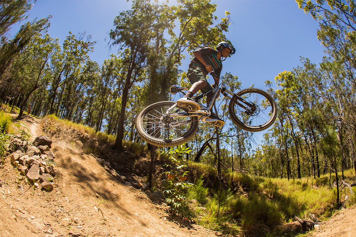 Mountain biker is airborne crossing a dry stony gully with open forest in the background.