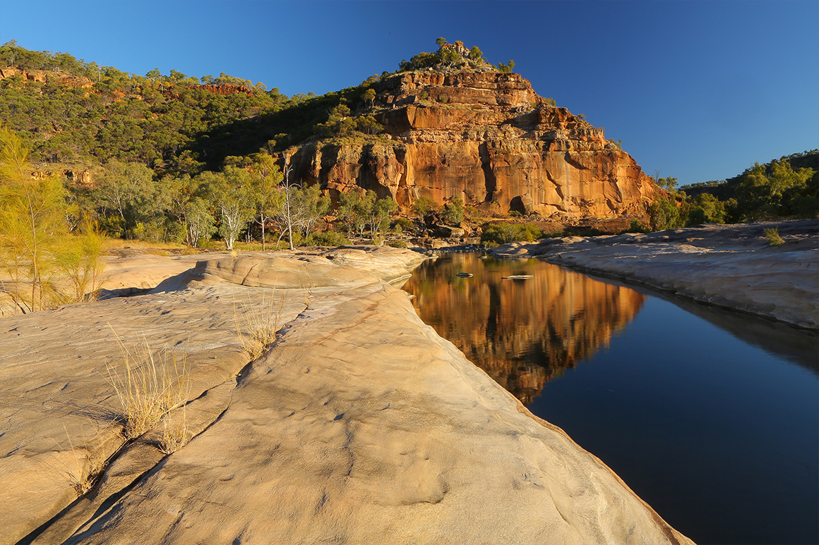 Smooth sandstone pyramid shaped stack is reflected in the blue waters of a deep creek.