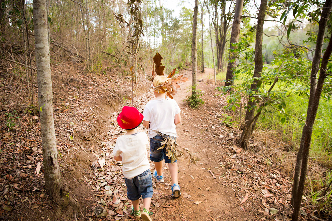 Two young children with hats walking along track with open forest each side of the track