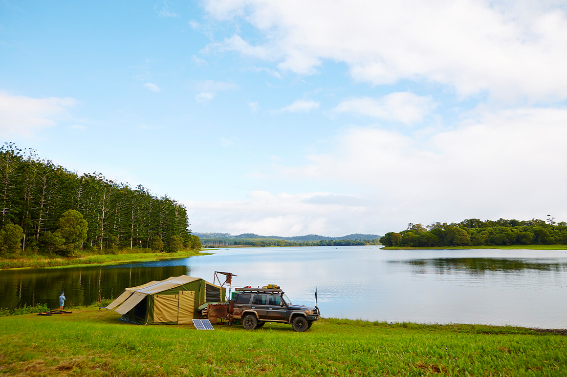 A four wheel drive vehicle is parked in front of a large tent, set on the grassy shore of a large forest-fringed lake, where the tranquil waters reflect the forest and blue skies above.